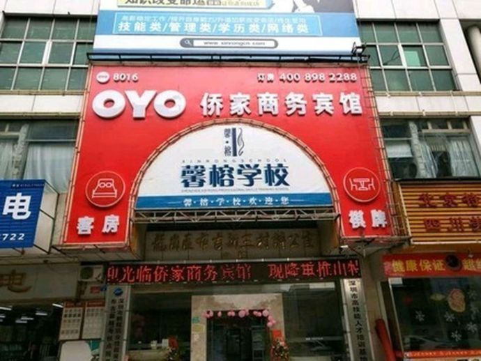 "Sign of a typical OYO branded hotel (colored in red) is shown in this picture. The Chinese letters after ""OYO"" represent the hotel's original name"