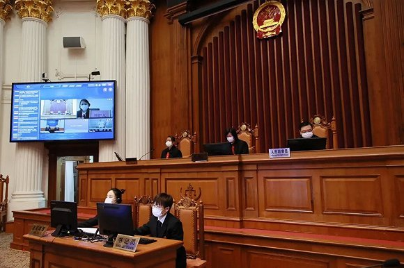 A court in Shanghai tries a case online during the epidemic. The public defender in a remote location can be seen on the upper right corner on the screen. Photo/Jiemian